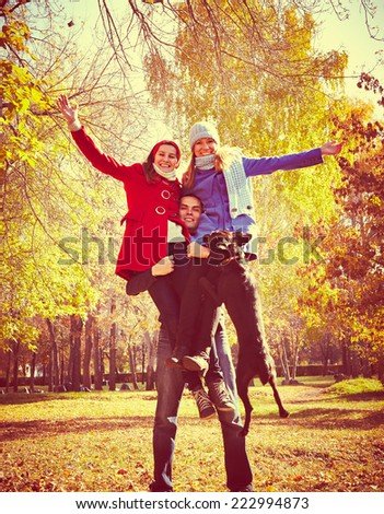 Portrait of happy man holding two women with dog -having fun at autumn fall  - stock photo