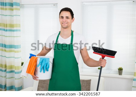 Portrait of happy man in green apron holding cleaning equipment at home - stock photo