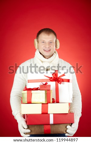 Portrait of happy man in white winterwear with stack of giftboxes looking at camera - stock photo