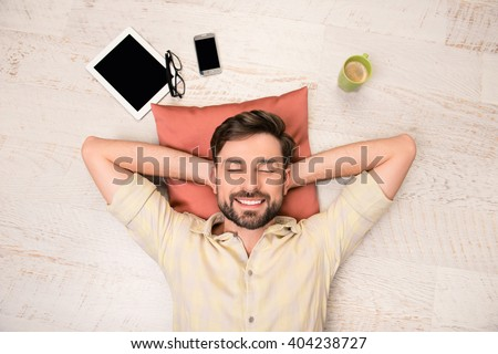 Portrait of happy man lying on floor and dreaming about smth - stock photo