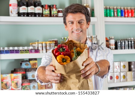 Portrait of happy man showing fresh bellpeppers in paper bag at grocery store - stock photo