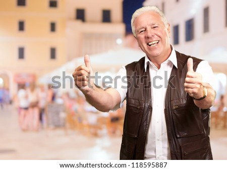 Portrait Of Happy Man Showing Thumb-up Sign, Outdoors - stock photo