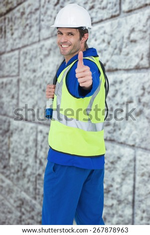 Portrait of happy man showing thumbs up against grey brick wall - stock photo