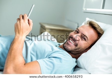Portrait of happy man using mobile phone while lying on bed at home - stock photo