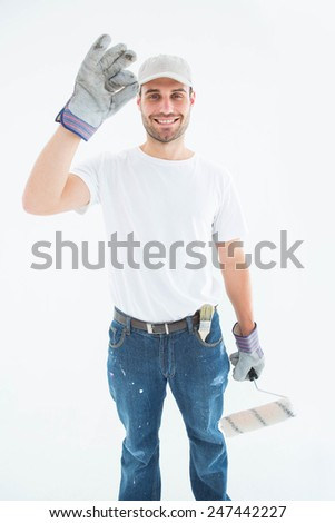 Portrait of happy man wearing gloves while holding paint roller on white background - stock photo