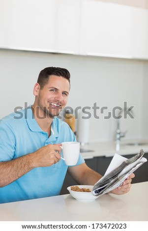 Portrait of happy man with newspaper drinking coffee at table in house - stock photo