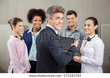 Portrait of happy manager in meeting with customer service representatives at call center - stock photo