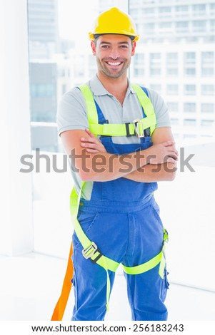 Portrait of happy manual worker wearing safety harness standing arms crossed in bright office - stock photo