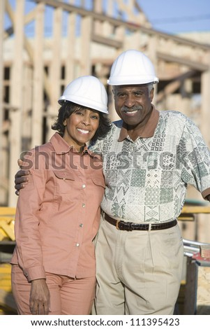 Portrait of happy mature African American couple wearing hardhat in front of incomplete house - stock photo