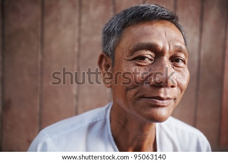 Portrait of happy mature asian man looking at camera against brown wall. Copy space - stock photo