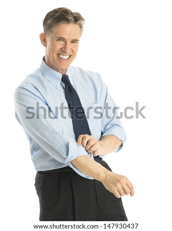 Portrait of happy mature businessman rolling up his sleeves while standing against white background - stock photo