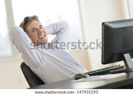 Portrait of happy mature businessman with hands behind head relaxing at desk in office - stock photo