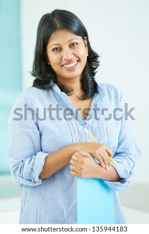 Portrait of happy mature businesswoman with document and pencil looking at camera - stock photo