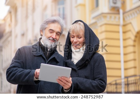 Portrait of happy mature caucasian couple using digital tablet outdoors - stock photo