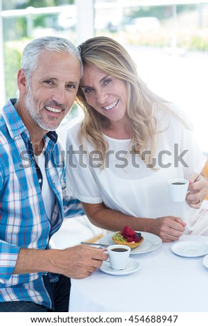 Portrait of happy mature couple holding coffee cup in restaurant - stock photo