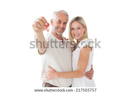 Portrait of happy mature couple holding new house key over white background - stock photo