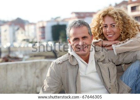 Portrait of happy mature couple in town - stock photo