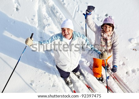 Portrait of happy mature couple of skiers laughing - stock photo