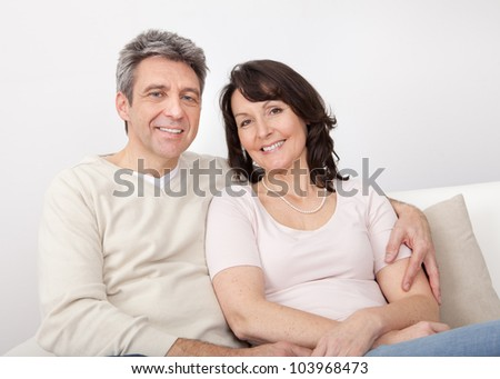 Portrait of happy mature couple sitting at home in the couch - stock photo