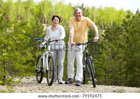Portrait of happy mature couple with bicycles looking at camera - stock photo