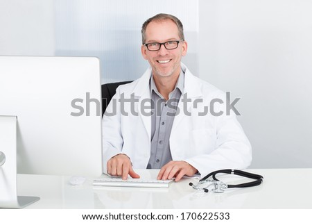 Portrait Of Happy Mature Doctor Using Computer In Clinic - stock photo