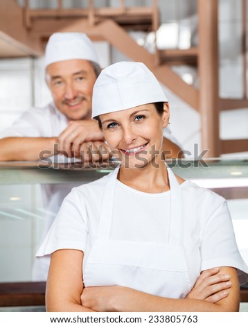 Portrait of happy mature female butcher with male colleague in background at butchery - stock photo