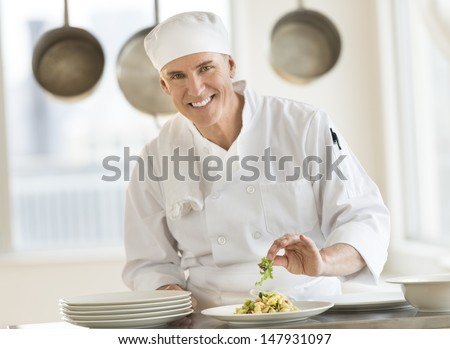Portrait of happy mature male chef garnishing pasta dish at counter in commercial kitchen - stock photo