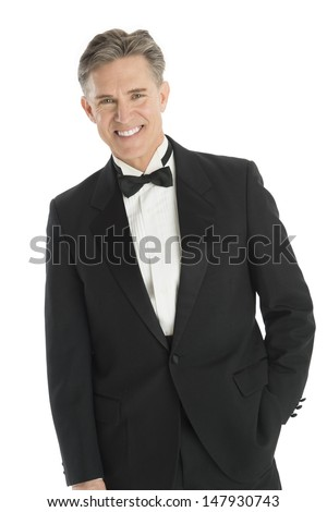 Portrait of happy mature man in tuxedo standing against white background - stock photo