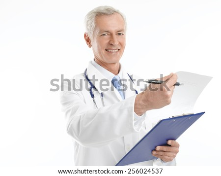 Portrait of happy mature medical doctor holding clipboard while standing against white background. - stock photo