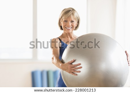 Portrait of happy mature woman holding yoga ball at home - stock photo