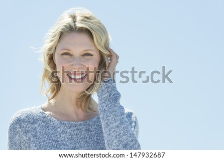 Portrait of happy mature woman with hand in hair against clear sky - stock photo
