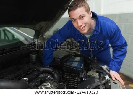 Portrait of happy mechanic repairing under car hood - stock photo