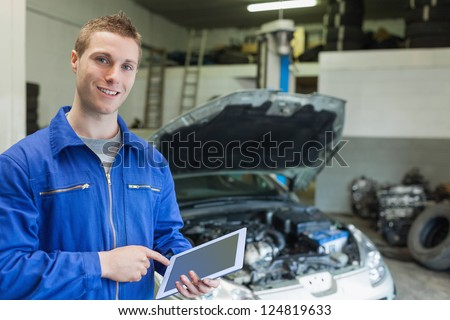 Portrait of happy mechanic using digital tablet in workshop - stock photo
