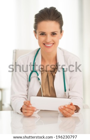 Portrait of happy medical doctor woman using tablet pc - stock photo