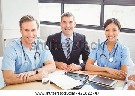 Portrait of happy medical team smiling in conference room in hospital - stock photo