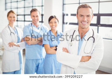 Portrait of happy medical team standing together with arms crossed in hospital - stock photo