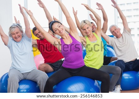 Portrait of happy men and women on fitness balls exercising in gym class - stock photo