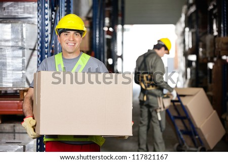 Portrait of happy mid adult foreman with cardboard box and coworker pushing handtruck at warehouse - stock photo