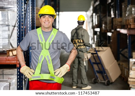 Portrait of happy mid adult foreman with hands on hips and coworker pushing handtruck at warehouse - stock photo
