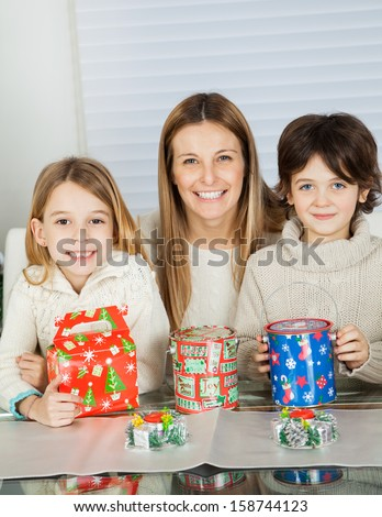 Portrait of happy mid adult woman and children with Christmas gifts at home - stock photo