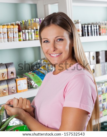 Portrait of happy mid adult woman in grocery store - stock photo