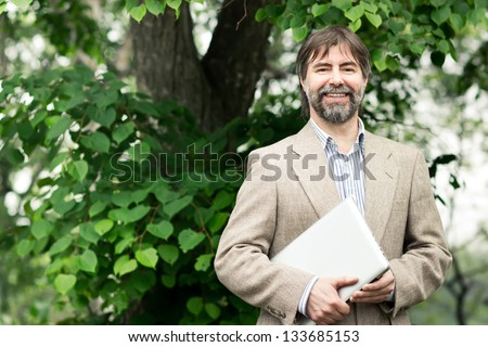 Portrait of happy middle-aged businessman holding notebook and smiling, outdoors - stock photo