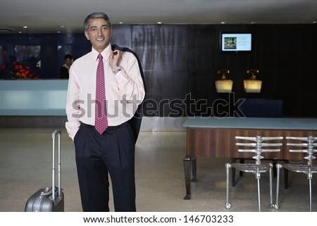 Portrait of happy middle aged businessman with luggage in hotel lobby - stock photo