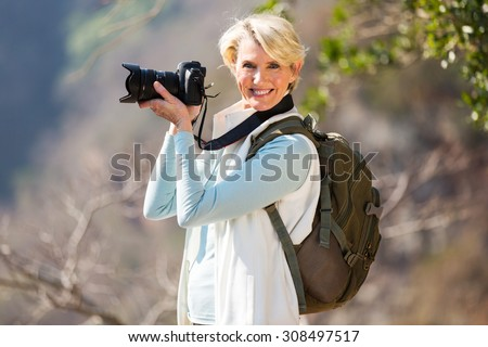 portrait of happy middle aged photographer on top of the mountain - stock photo