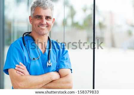 portrait of happy middle aged surgeon with arms folded - stock photo