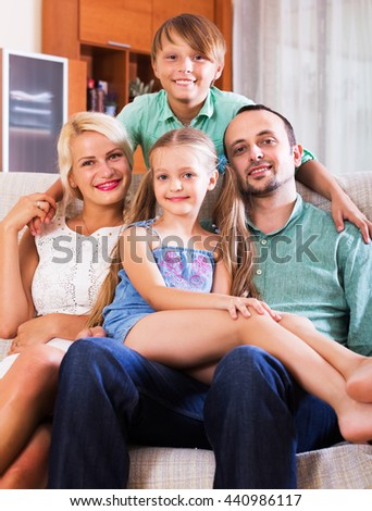 Portrait of happy middle class caucasian family with two children at home interior. Focus on girl - stock photo
