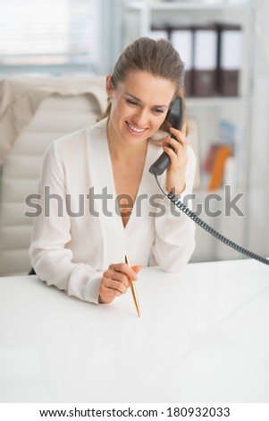 Portrait of happy modern business woman talking phone in office - stock photo
