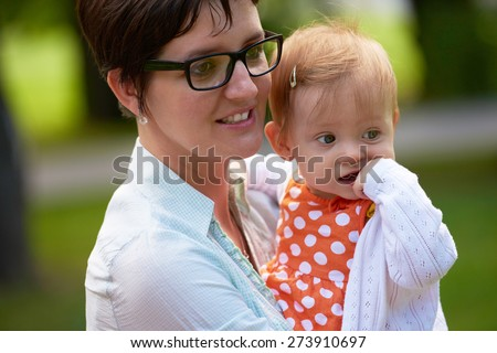 portrait of happy mom and baby daughter smiling at park nature - stock photo
