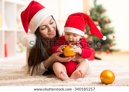 Portrait of happy mother and adorable baby holding bauble against domestic festive backdrop with Christmas tree - stock photo