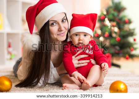 Portrait of happy mother and adorable baby in suit of Santa - stock photo